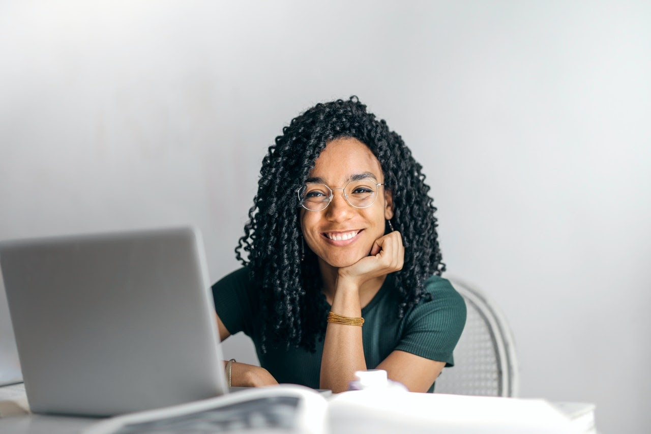 girl sitting at laptop smiling