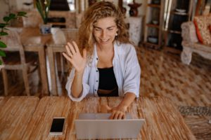 woman waving to online tutor