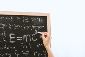 writing formulae on chalkboard