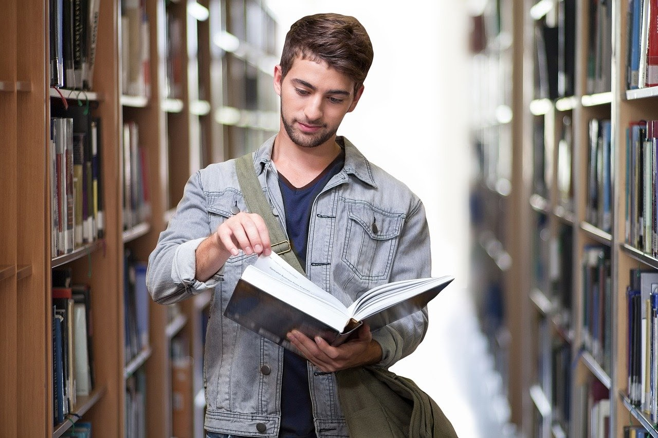 young man in library reading a book