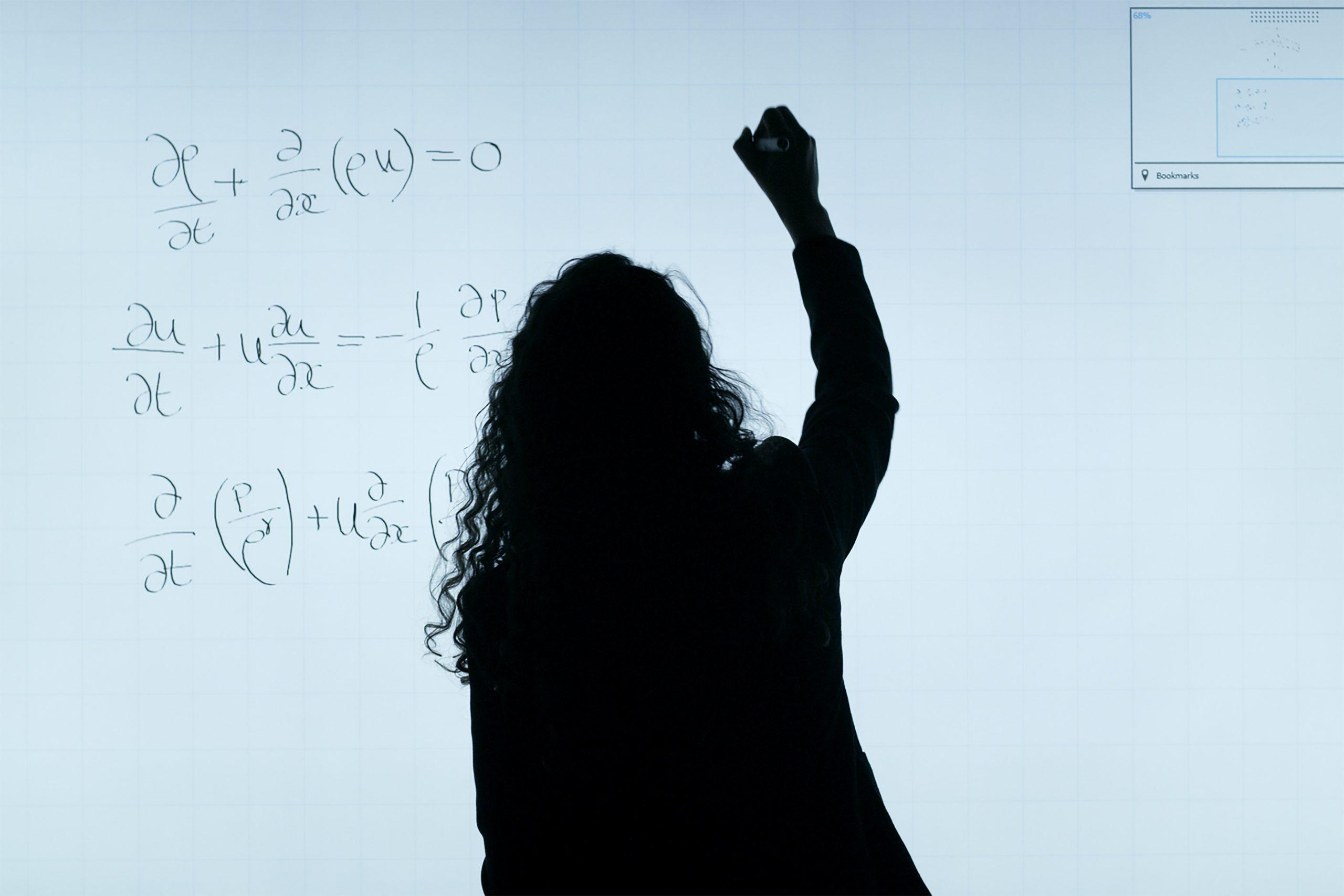 teacher writing equation on board