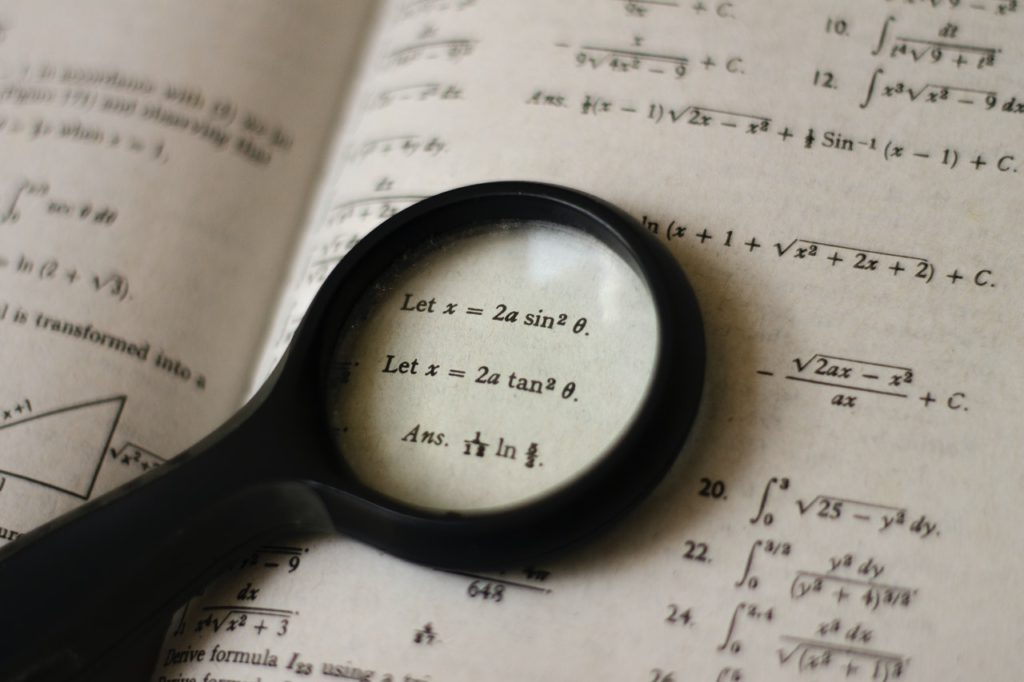 Equations in book with magnifying glass