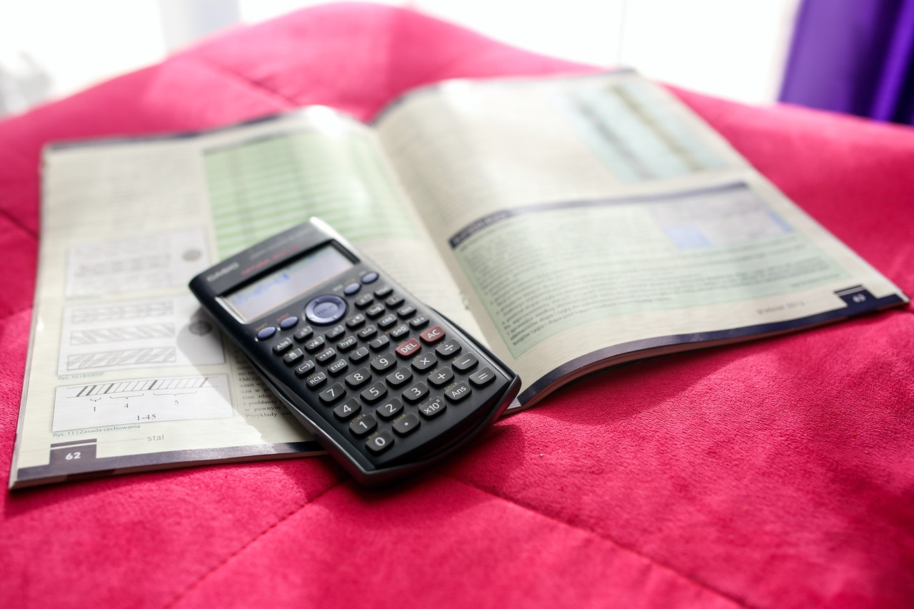 calculator and maths book on pink rug