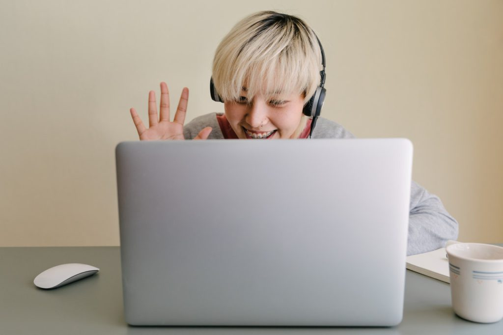 Student waving at laptop screen