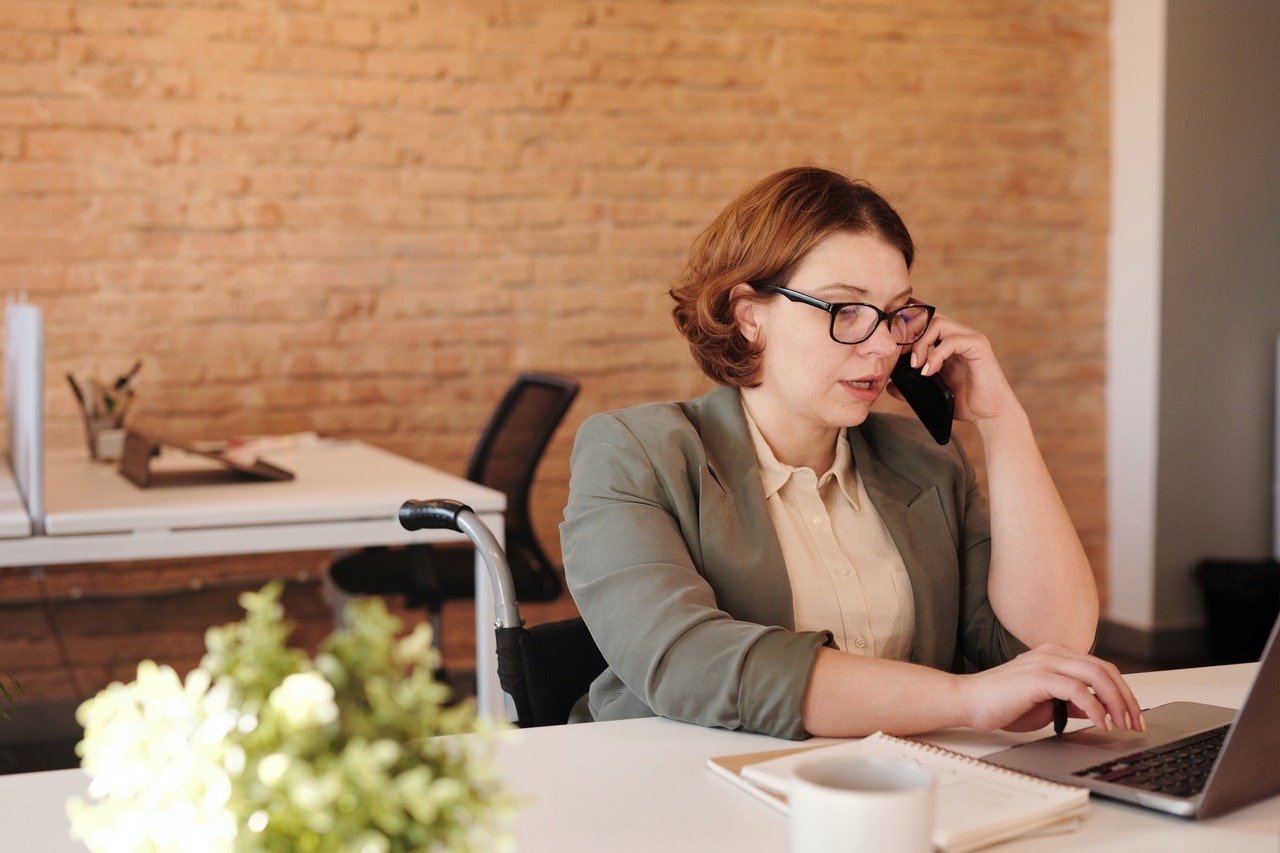 Woman sitting at desk on phone
