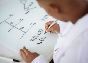 Woman using white board for equations