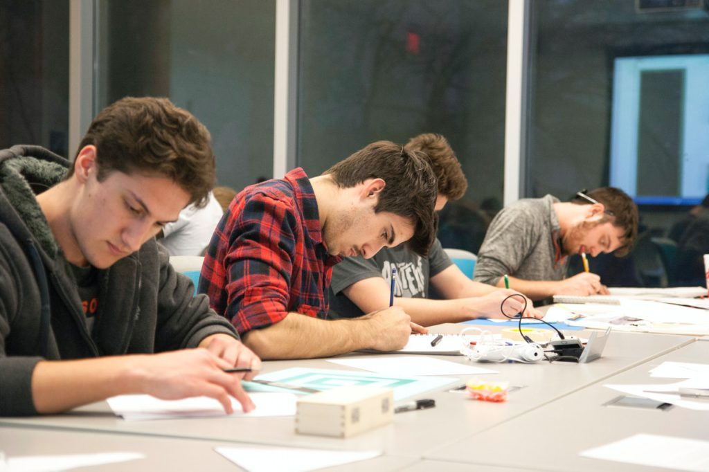male students writing in classroom