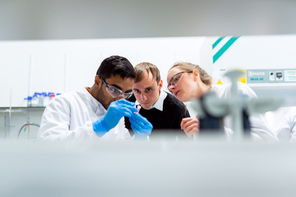 three lab assistant looking at sample