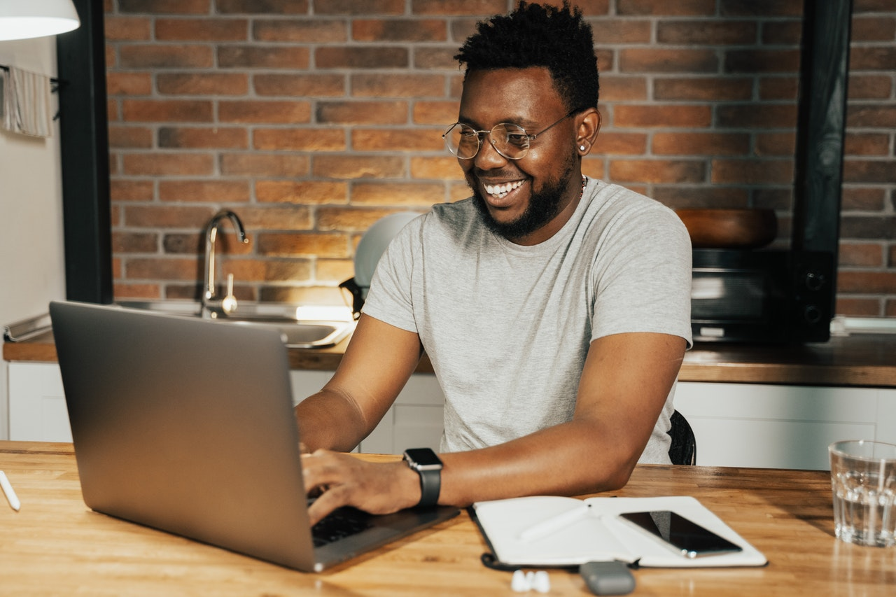 Man smiling whilst using laptop