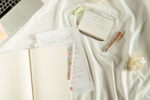 notebooks and pens on bed