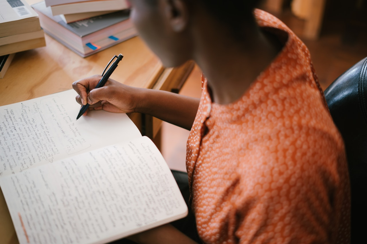 girl writing notes on book