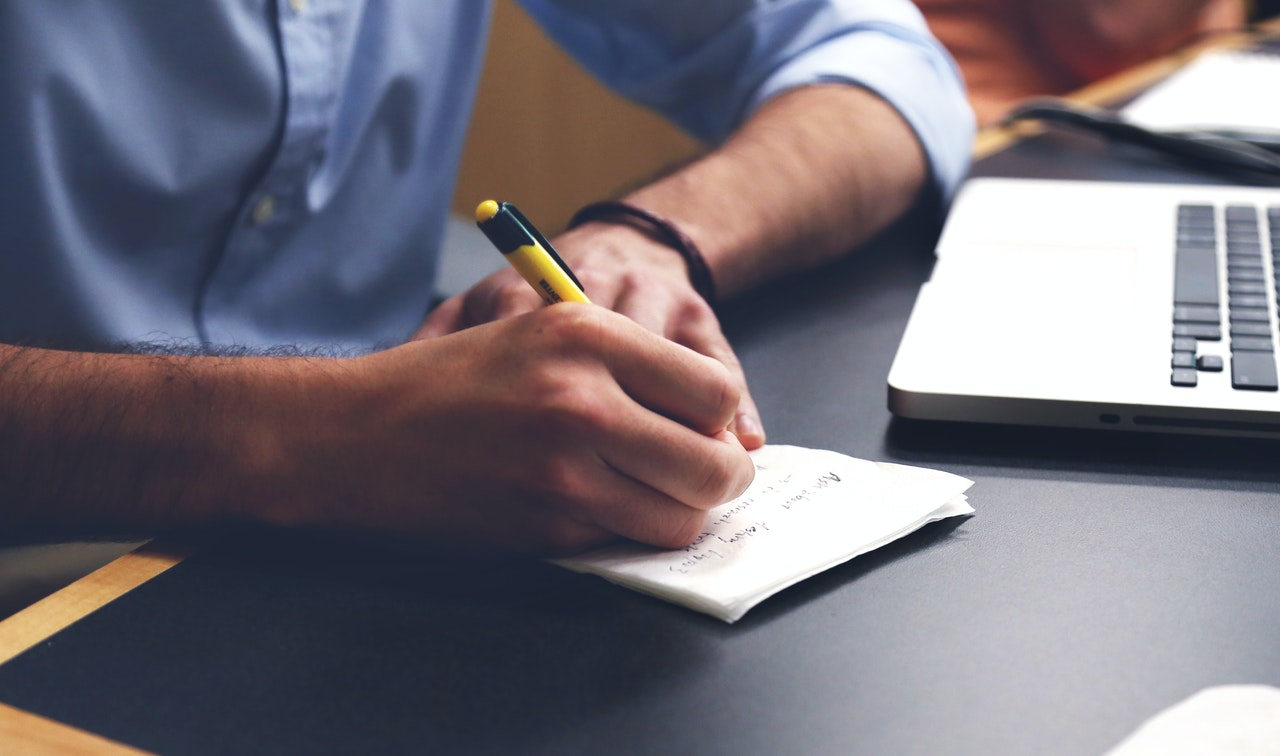 man writing on note pad on desk