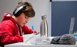 Child doing homework with headphones on